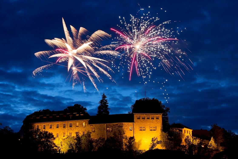 Ein Feuerwerk zur Hochzeit erstrahlt hoch oben die Creuzburg mit vielen verschiedenen Farben und Formen